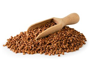 Pile of buckwheat and wooden spoon