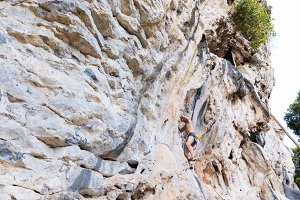 Young man rock climbing on white mou