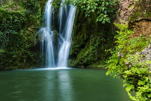 Big waterfall falling to pond in the