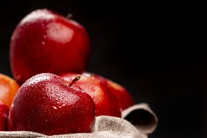 Wet red apples in bowl on darkness