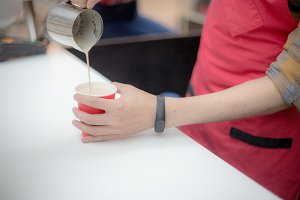 Barista in a red apron pours coffee