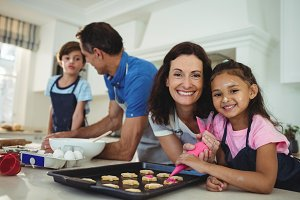 Happy family preparing cookies in ki
