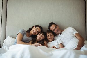 Parents and kids sitting on the bed