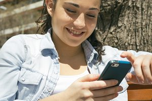 Young woman smiling using her phone
