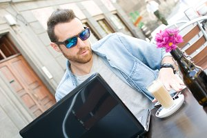 young man with a laptop and a coffee