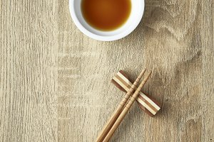Chopsticks and soy sauce on wooden