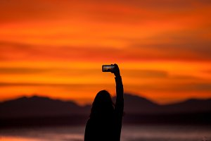 Woman photographs Sunset with Phone