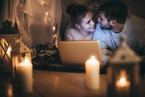 Romantic couple on bed with a laptop