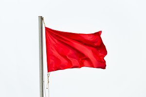 Red flag waving isolated over white