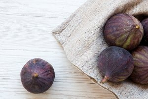 Fresh figs in a bowl on a white wood