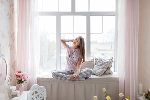 Girl in pajama on windowpane