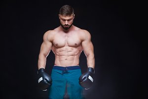 Strong muscular boxer in black