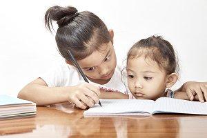 Two little girls thai homework