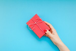 Woman hand holding red present gift