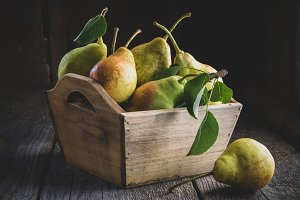 Fresh ripe pears in a wooden crate.