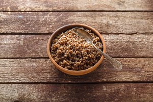 Bowl with cooked buckwheat on old