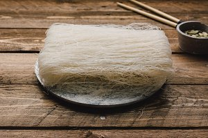 Uncooked rice noodles, on rustic woo