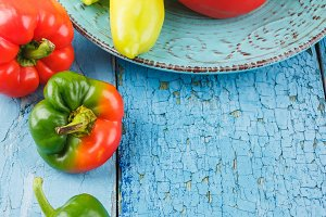 Colored peppers on the blue ceramic