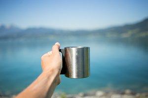 Woman holds simple metal camping mug