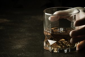 Whiskey glass in hand on the dark ba
