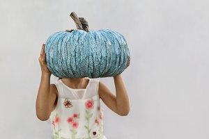 A Little Girl Holding Blue Pumpkin
