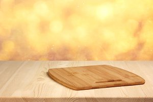 Empty wooden table on blurred gold a