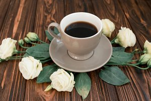 Coffee and flowers on a rustic wood
