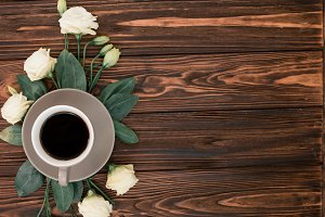 A cup of coffee and flowers flat lay