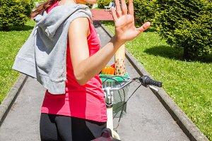 Sportive woman with bike waving
