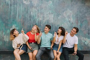 Happy group teenagers show something