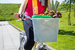 Woman with groceries in basket bike
