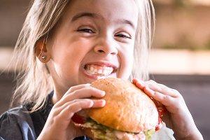 A little girl eats a sandwich
