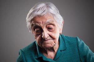 Sad elderly woman looking down