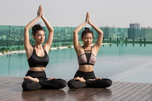 Two attractive women are playing yog