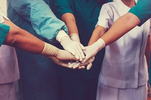 Doctors and nurses coordinate hands.