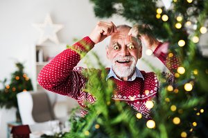 A senior man standing by Christmas