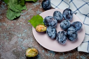 Fresh picked plums in ceramic plate