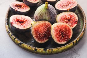 Fresh purple figs on a green dish