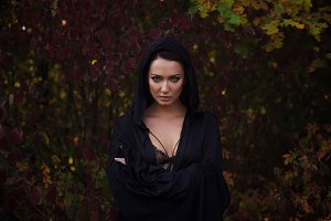 Young woman in the black cloak in th