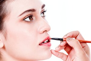 Stylist applying red lip gloss