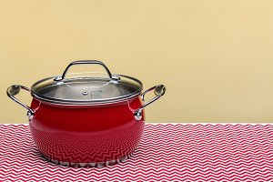 Red kitchen pot with lid, isolated