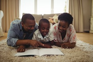 Parents and son reading a book