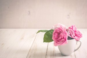 Pink tea roses on white wooden table