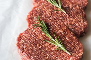 Raw beef patties on the white parchm