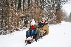 Grandfather and small girl sledging