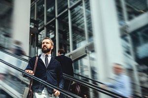 Hipster businessman using escalator