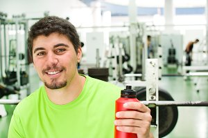 man drinking water in gym