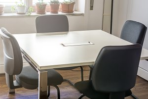 four empty chairs in a meeting room