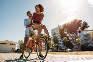 Couple riding bicycle in street