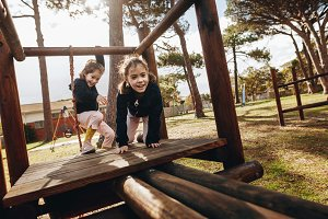 Twin sisters enjoying at playground